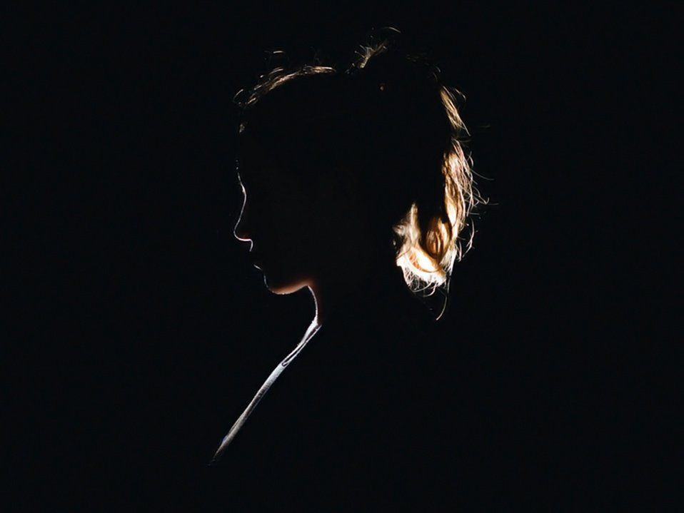 A side profile, silhouette of a young woman with a ponytail, her head slightly tilted down.
