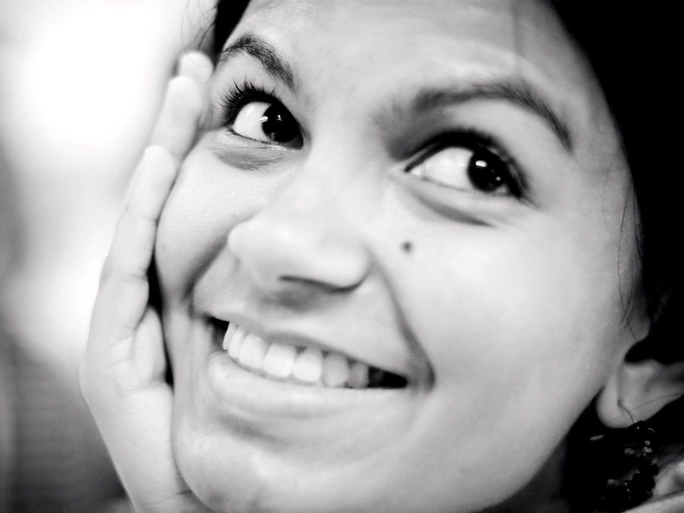 A closeup of a young woman's face, smiling, looking up at the camera, with her right hand cupping her right cheek.