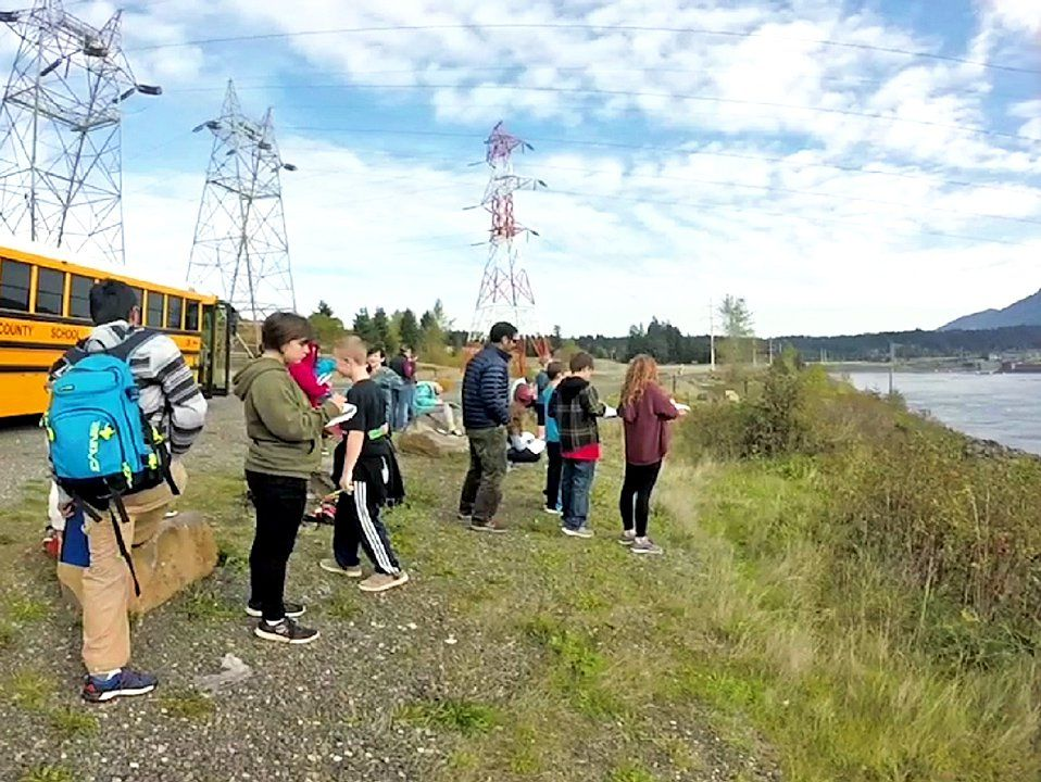 A class off the school bus next to the river taking notes