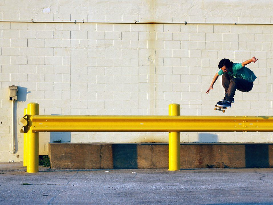A young teenage boy in a teal t-shirt and brown pants is in the air on a skateboard. Both of his arms are extended out to his sides and his knees are up to his chest. He's hovering over a yellow beam against an off-white brick wall.