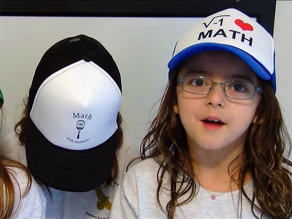 "Three young girls are standing beside each other wearing hats that say, ""I heart math."""