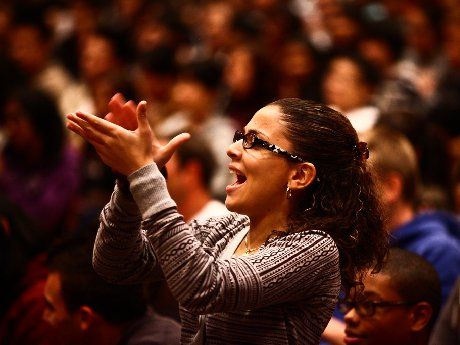 An adult woman is standing and clapping among a crowd of people sitting.