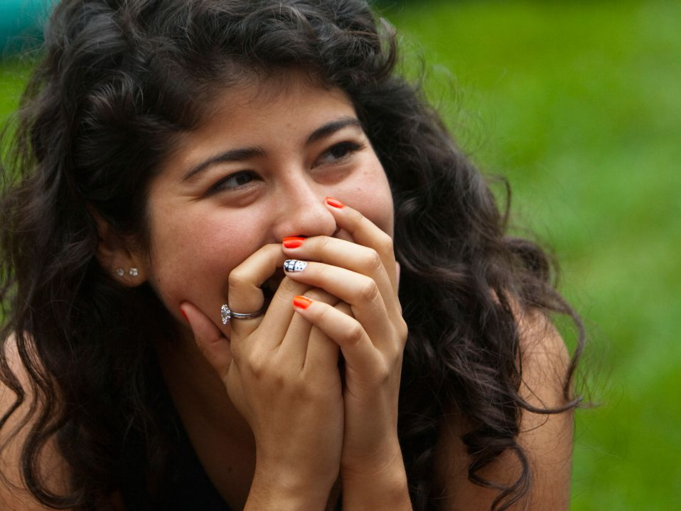 A closeup of a teenage girl with long, brown, curly hair, smiling, her hands covering her mouth.
