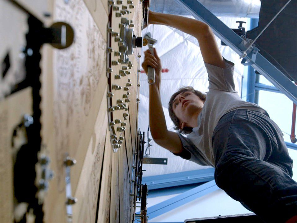 A low angle shot of a young teen boy leaning against a large wooden clock, more than twice his size, using a wrench.