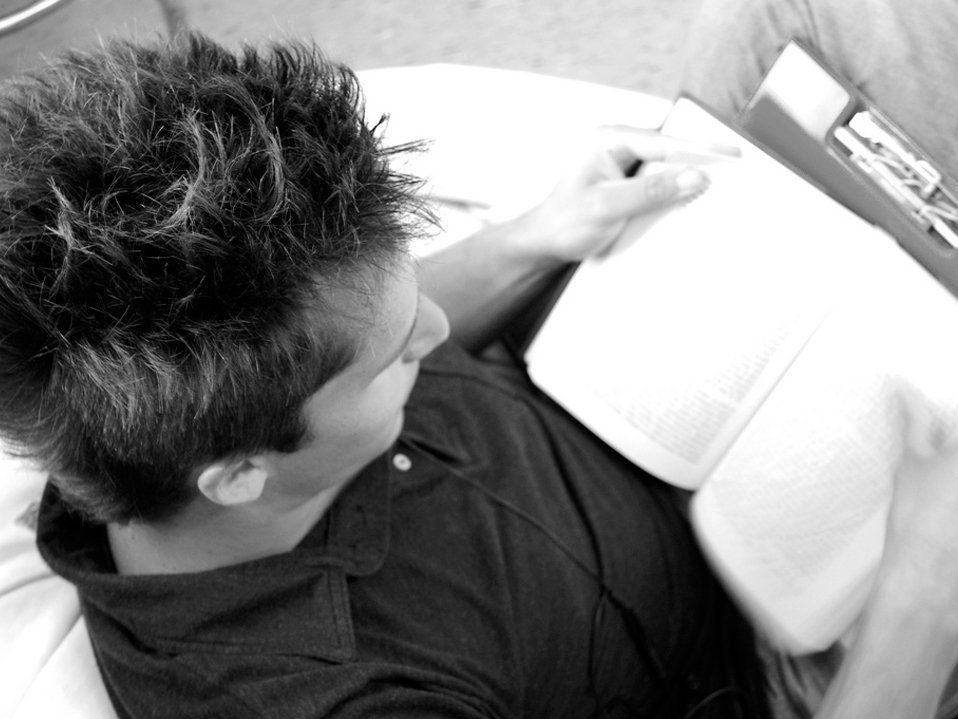 A person is sitting on a bean bag chair, reading.