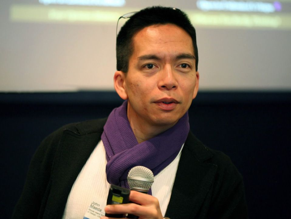 An adult male is sitting, holding a microphone, and speaking to someone. He's wearing glasses perched on top of his head, a white top, black coat, purple scarf, and a conference name tag on his chest.