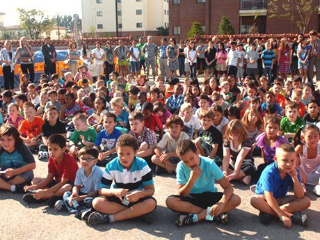 A lot of young students are sitting outside on a blacktop, with teachers standing behind them, all facing the same direction.