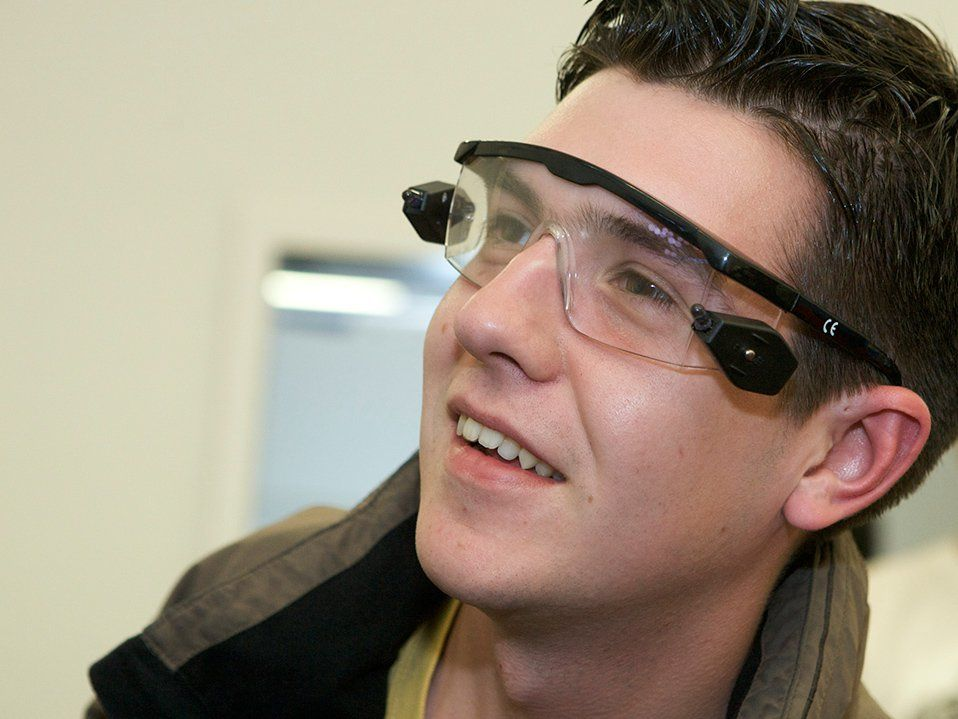 A closeup of a high school boy's face. He's smiling, looking off to the side, wearing tech goggles.