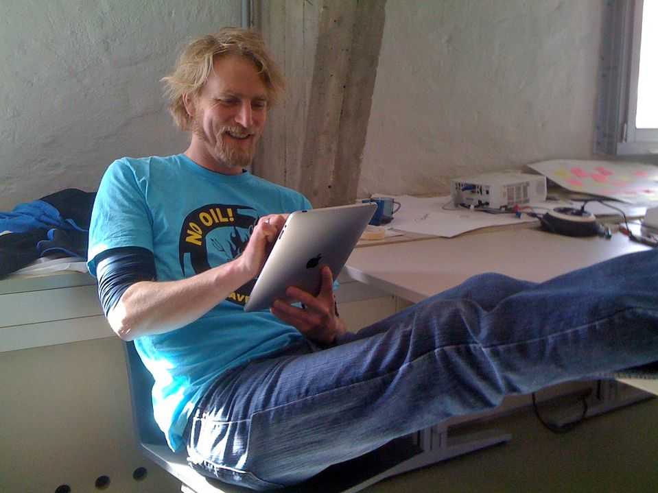 A man is sitting reclined in his sit with his legs on his desk, smiling, using his iPad.