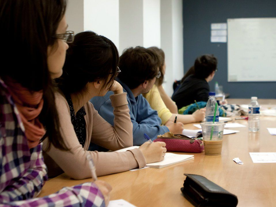 Six young adults are sitting on one side of a conference table looking towards the front of the room where a man is pointing at a whiteboard.