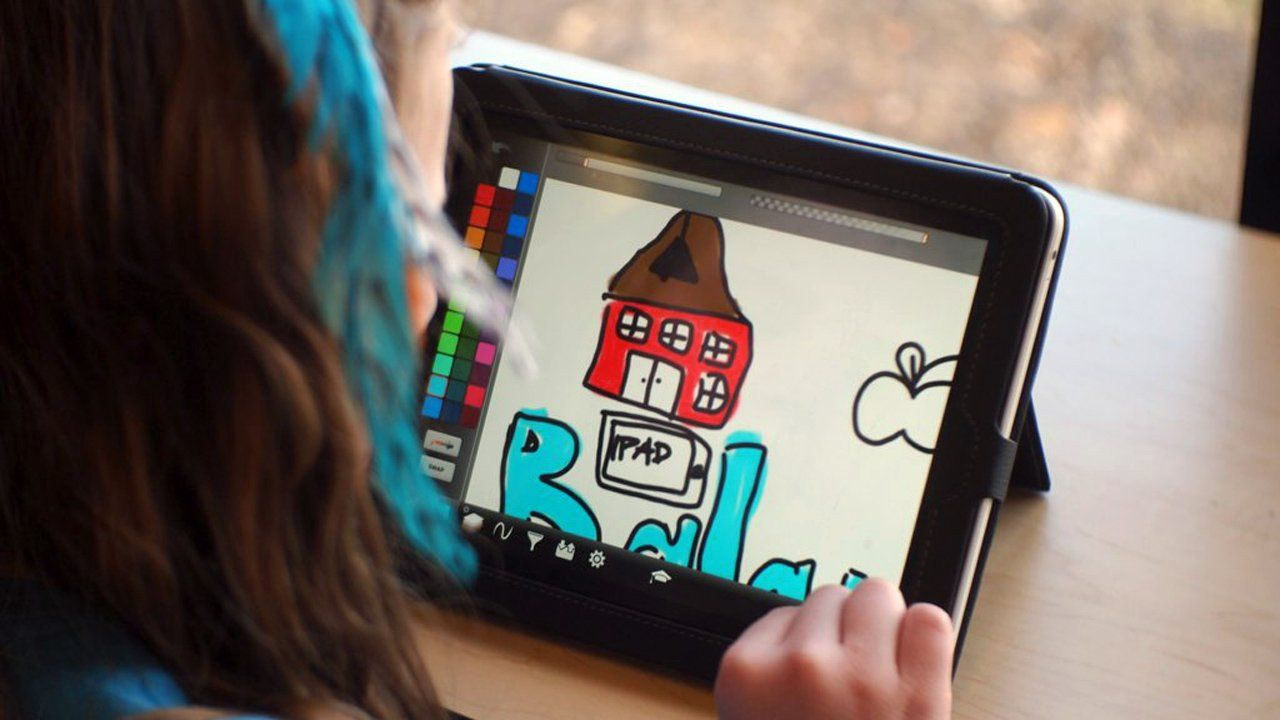 A girl is sitting at a desk looking at a tablet. We only see the back of her head. On the tablet screen is a color palette and a drawing of a brown and red farm.