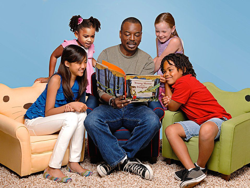 LeVar Burton, associated with Reading Rainbow, is sitting on a blue couch chair reading a book to four kids. A girl is sitting on a cat chair to his left, a boy is sitting on a frog chair to his right, and two girls are standing behind them.