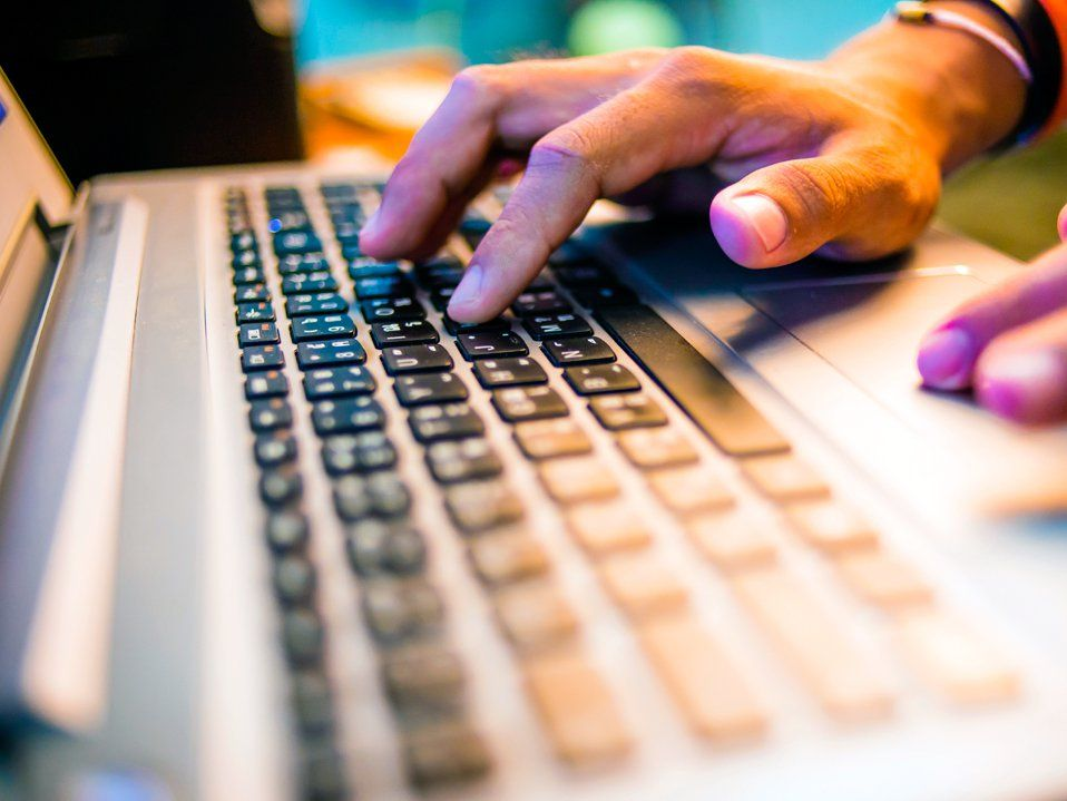 A closeup of a person's hands on a laptop keyboard.