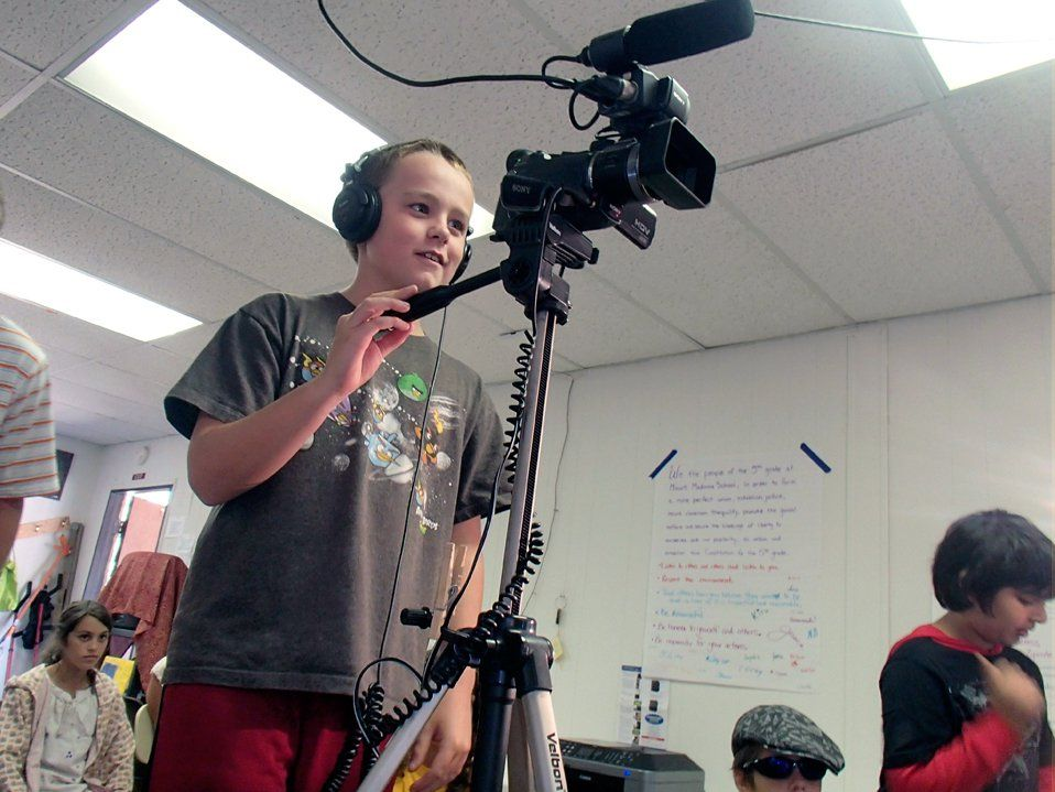 Boy wearing headphones standing in class operating a camera on a tripod