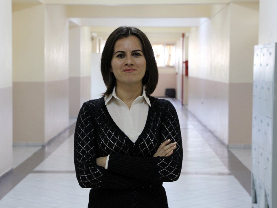 A closeup, waist up, of a female teacher standing in a school hallway. She's looking directly at the camera, her arms crossed, wearing a closed mouth smile. She's wearing a black blouse over a white, collared, button up.