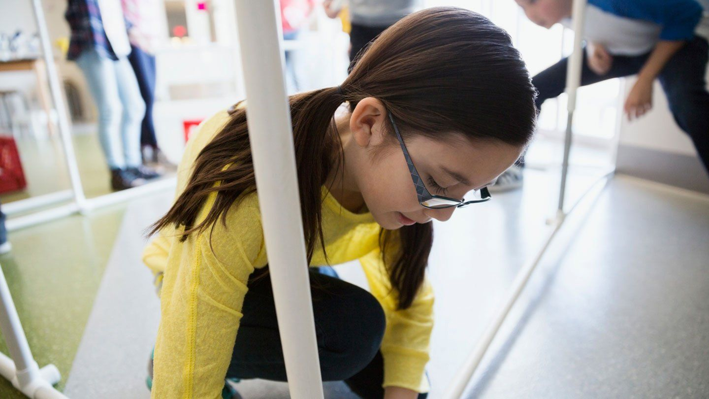A closeup of a young girl with pigtails in a yellow long sleeve shirt, black pants, and glasses kneeling down, connecting white tubes together, creating a table with a young boy who is squatting.