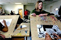 Intern Katie Osediacz checks a student's progress in art class.