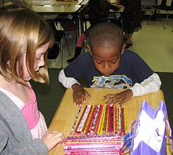 Attention, Shoppers: Students choose pencils after handing over the correct amount of play money.