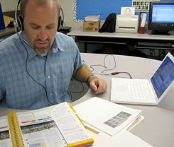 Practicing What He Teaches: Brent Coley references a class textbook to record a StudyCast, a podcast he records for his students as an audio review for their social studies and science tests.
