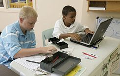 Funds for the Future:  Jacob (left) adds up banking deposits while Ray enters the amounts into the computer at the student-run CP Federal Credit Union in the Jackson, Michigan, YMCA.