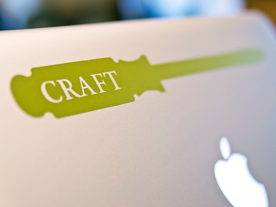 "A closeup of the back of a Mac laptop showing the apple icon and a green sticker of a screwdriver that says, ""Craft"" in white lettering."