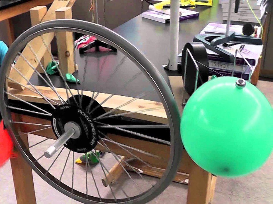 A bicycle wheel and balloon make up part of a Rube Goldberg machine.