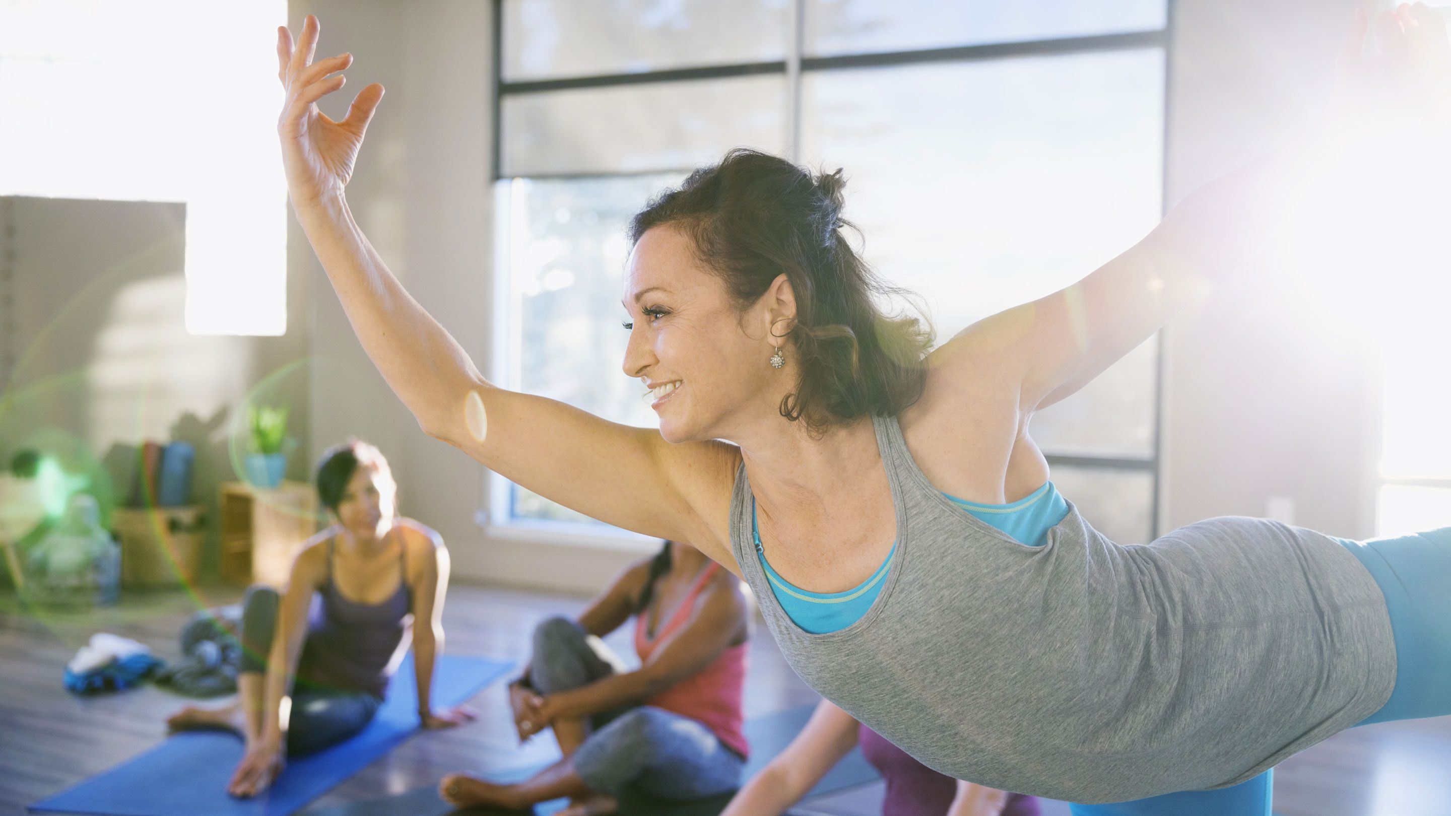 A smiling woman in a yoga class standing on one leg and both arms are extended.