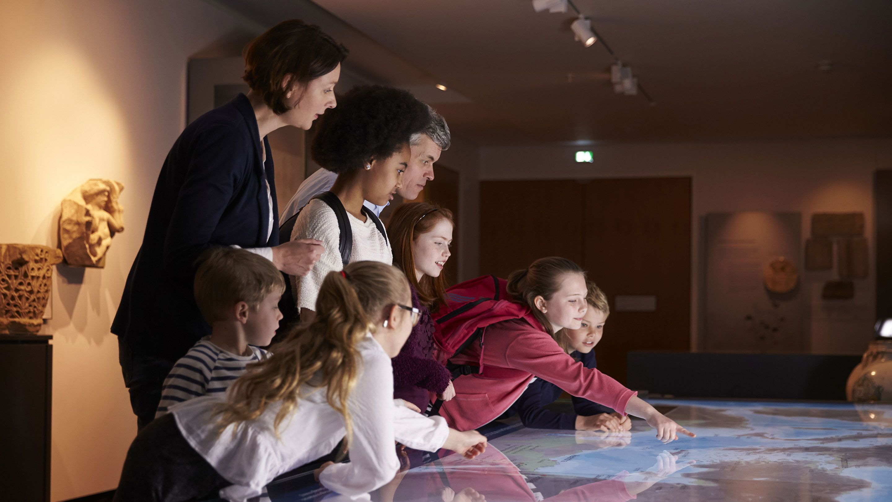 A group of students and teacher look at an illuminated table map.