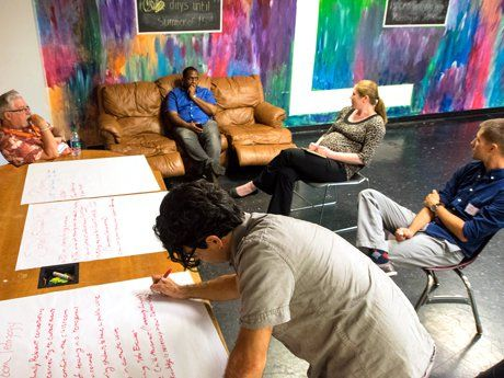 Five teachers in the lounge in discussion while one takes notes