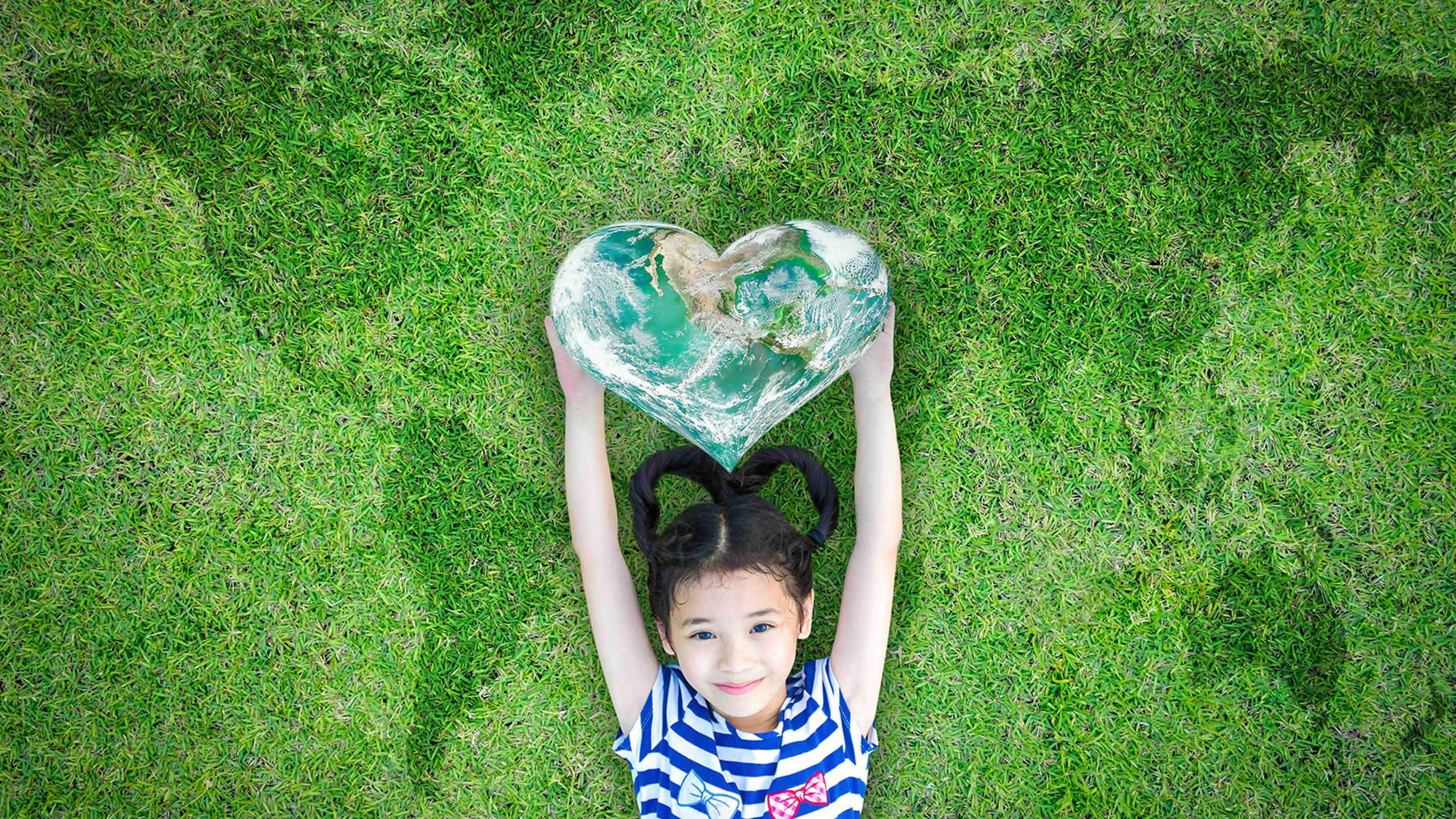 Young girl lying down, smiling, in the grass with heart-shaped globe above her head.