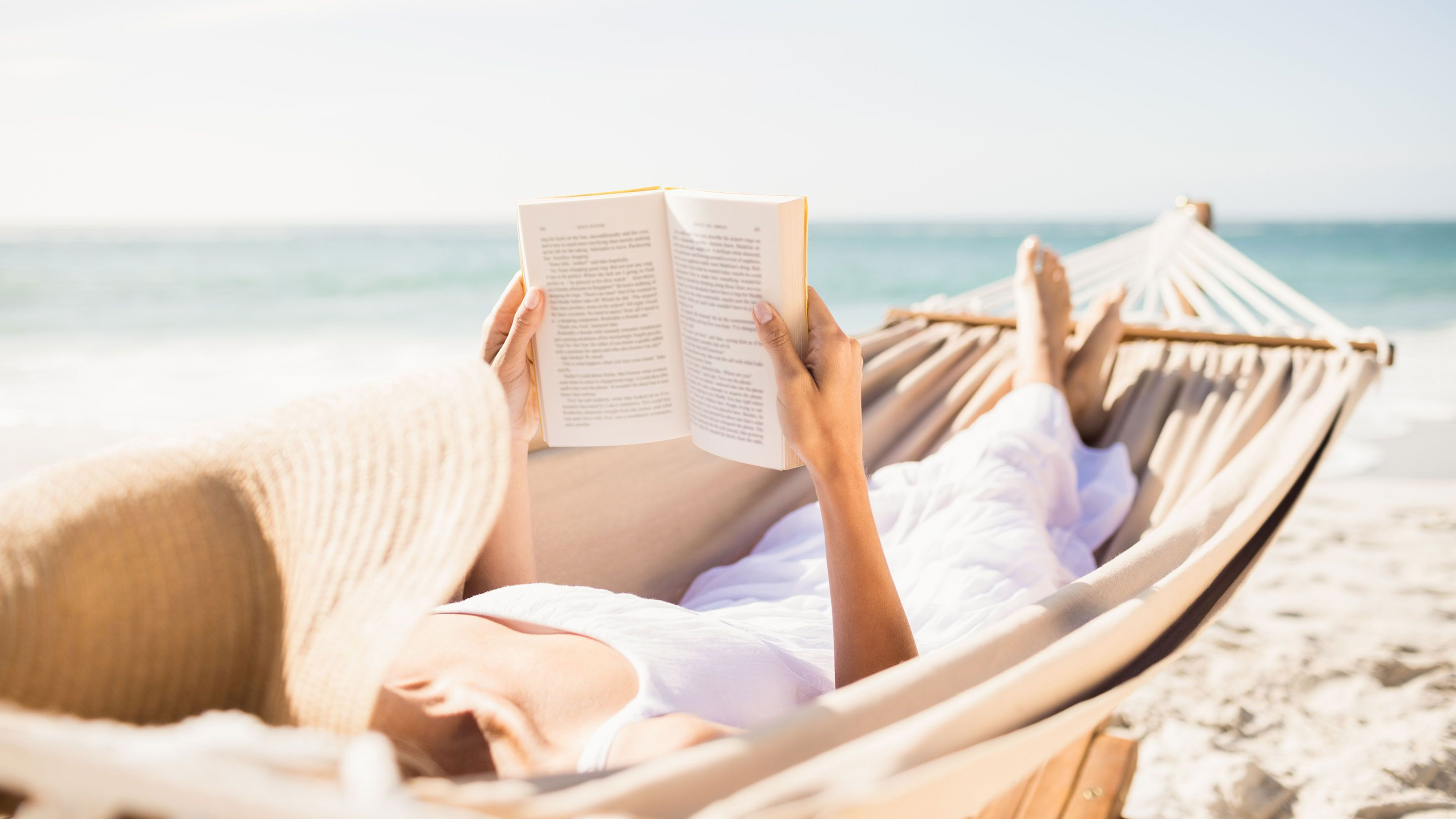 Woman on the beach reading and lounging in a hammock.