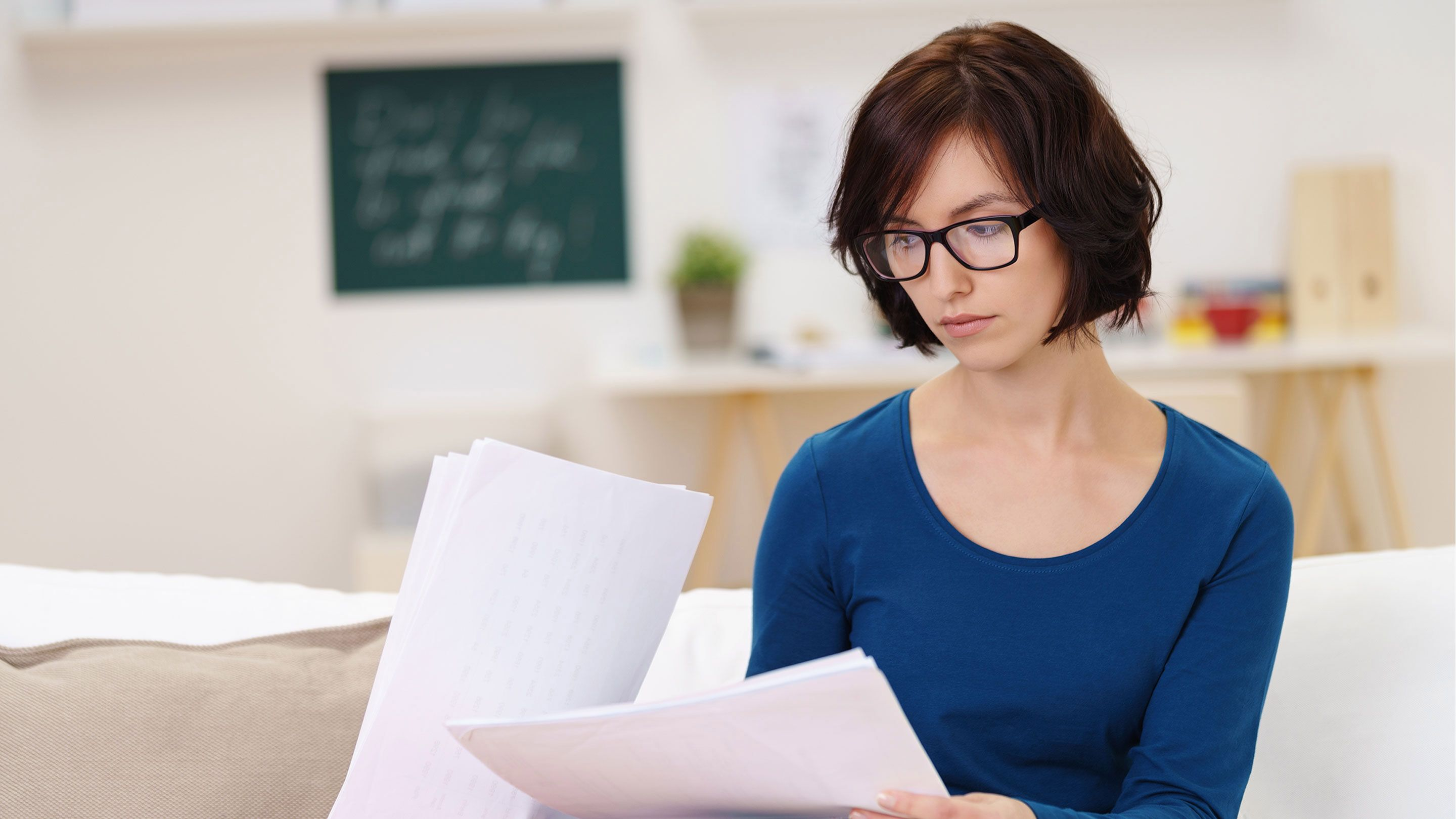 A female teacher in a blue shirt and glasses is sitting in a classroom alone, looking at papers.