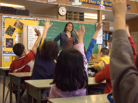 Teacher standing in front of class with students' hands raised