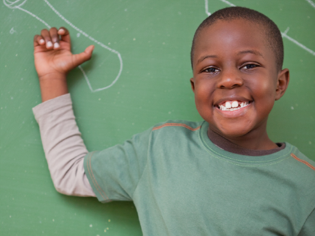 A photo of an elementary-school boy in front of a green chalkboard, smiling.
