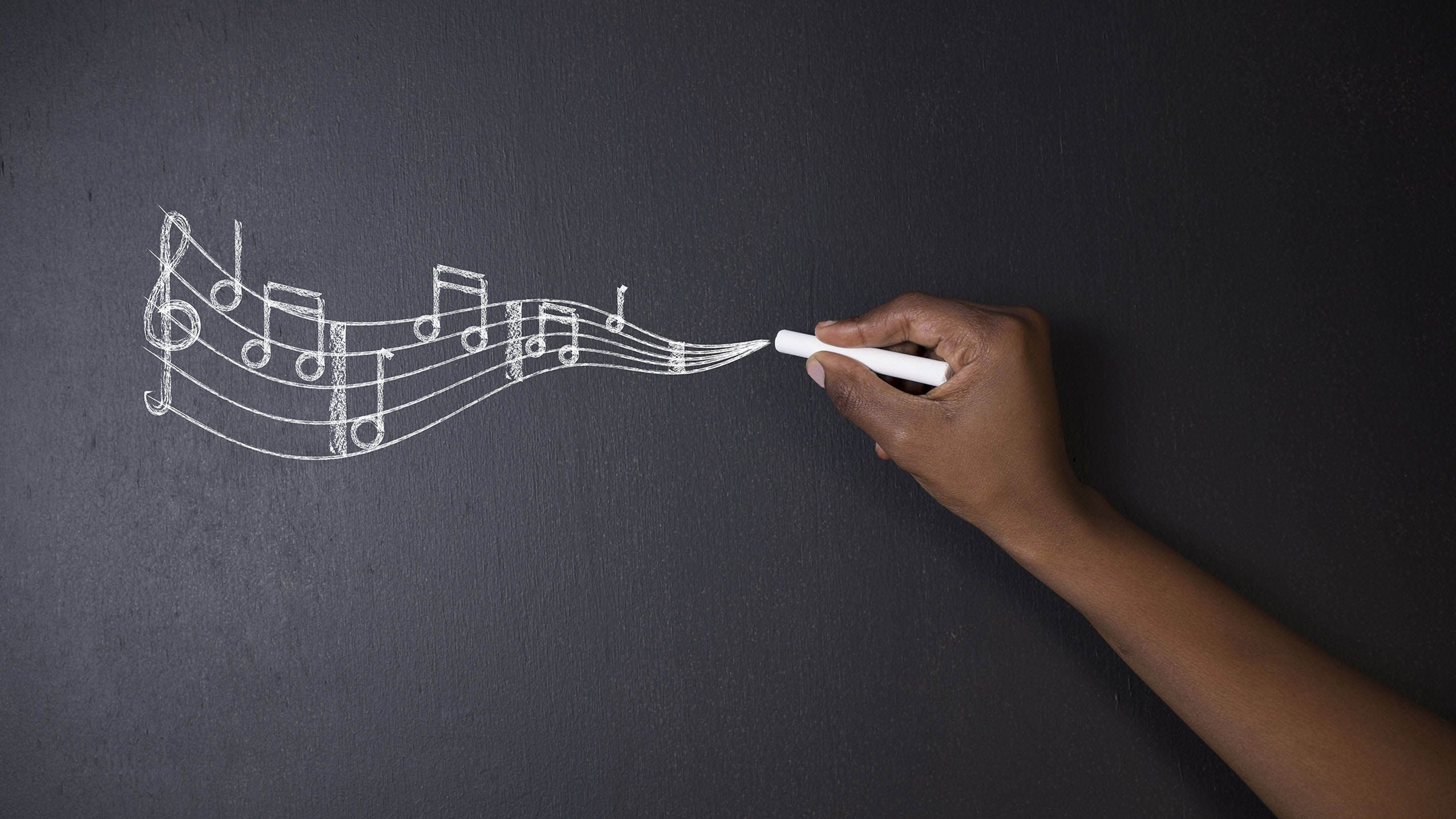Musical notes flow across a blackboard from a piece of chalk held by a student.