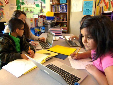 Teacher working with young students on laptops