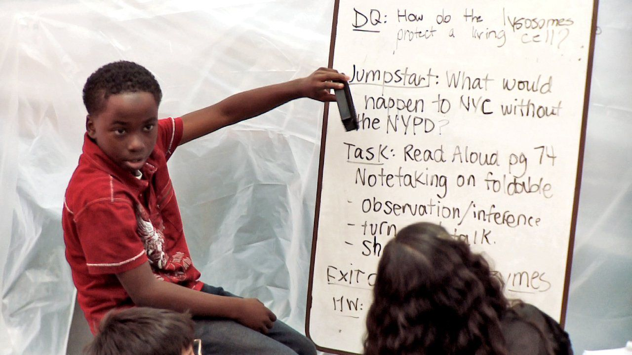 Boy sitting on a stool pointing to a white board speaking with other students looking on