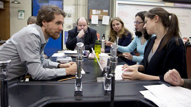 Six adults in the science lab classroom sitting around a table in discussion