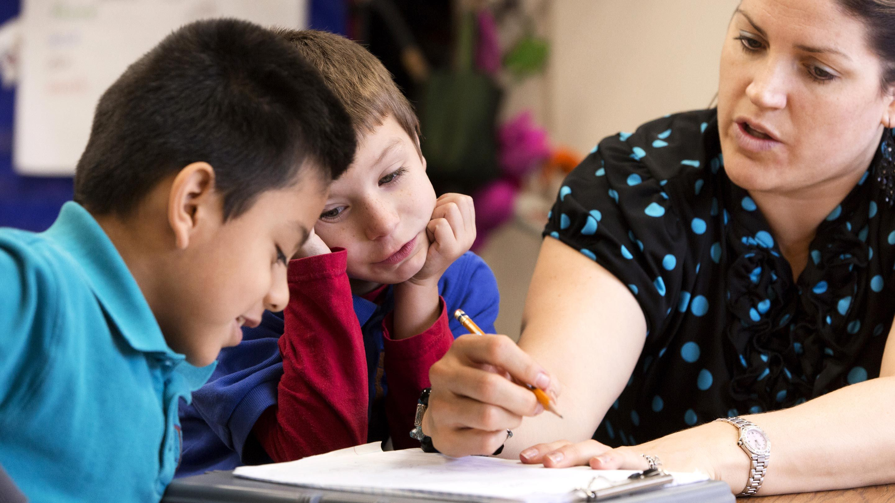 A teacher discusses writing feedback with two students.