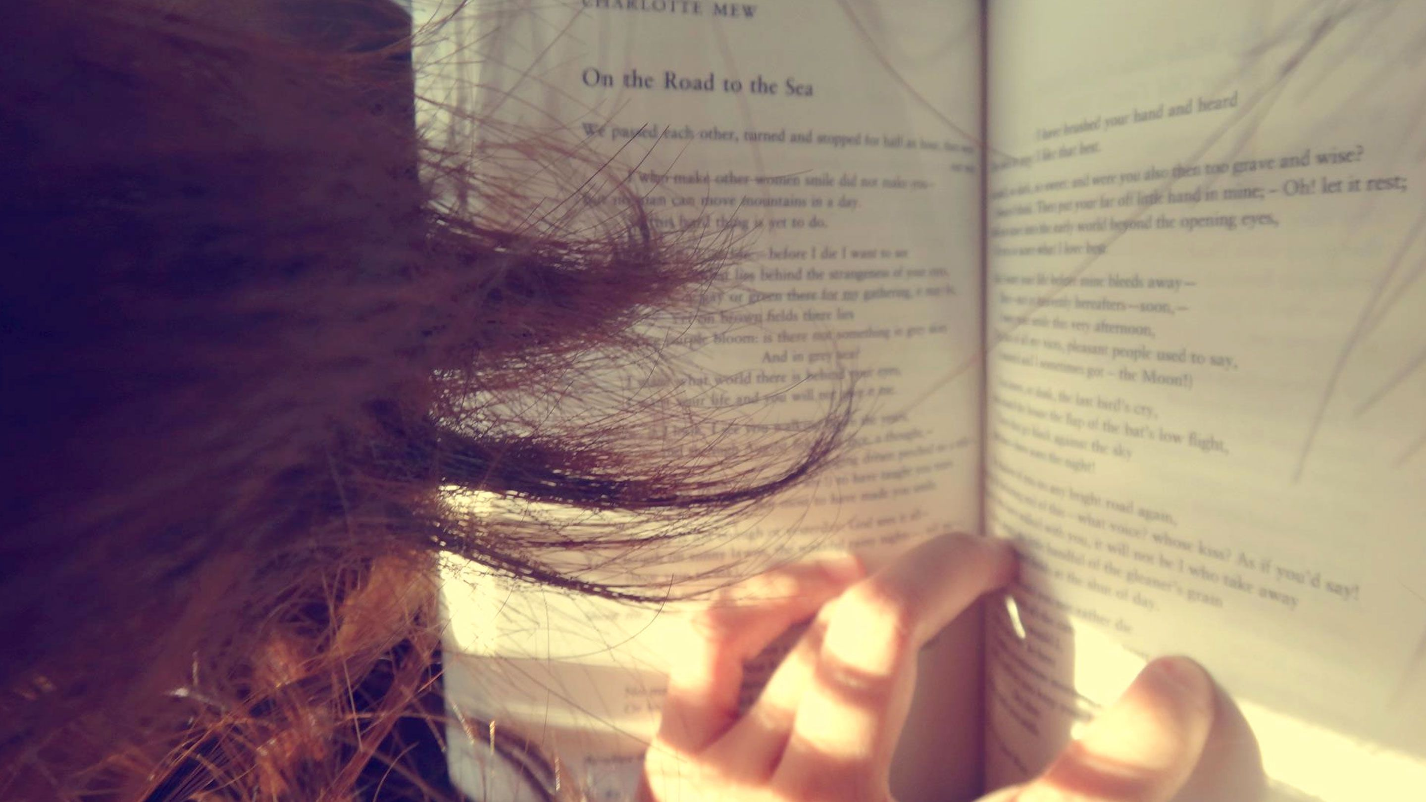 Photograph of an open book of poetry shot over the shoulder of a person with long hair