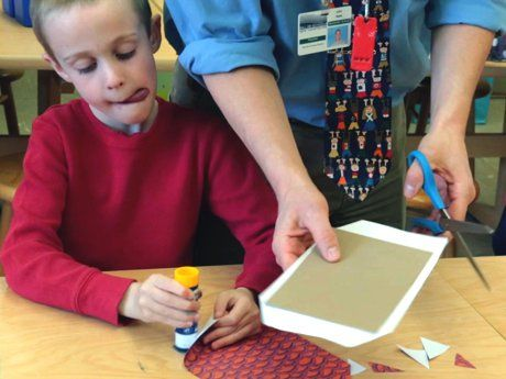Boy sitting with tongue out gluing with great concentration; teacher standing next to him using scissors
