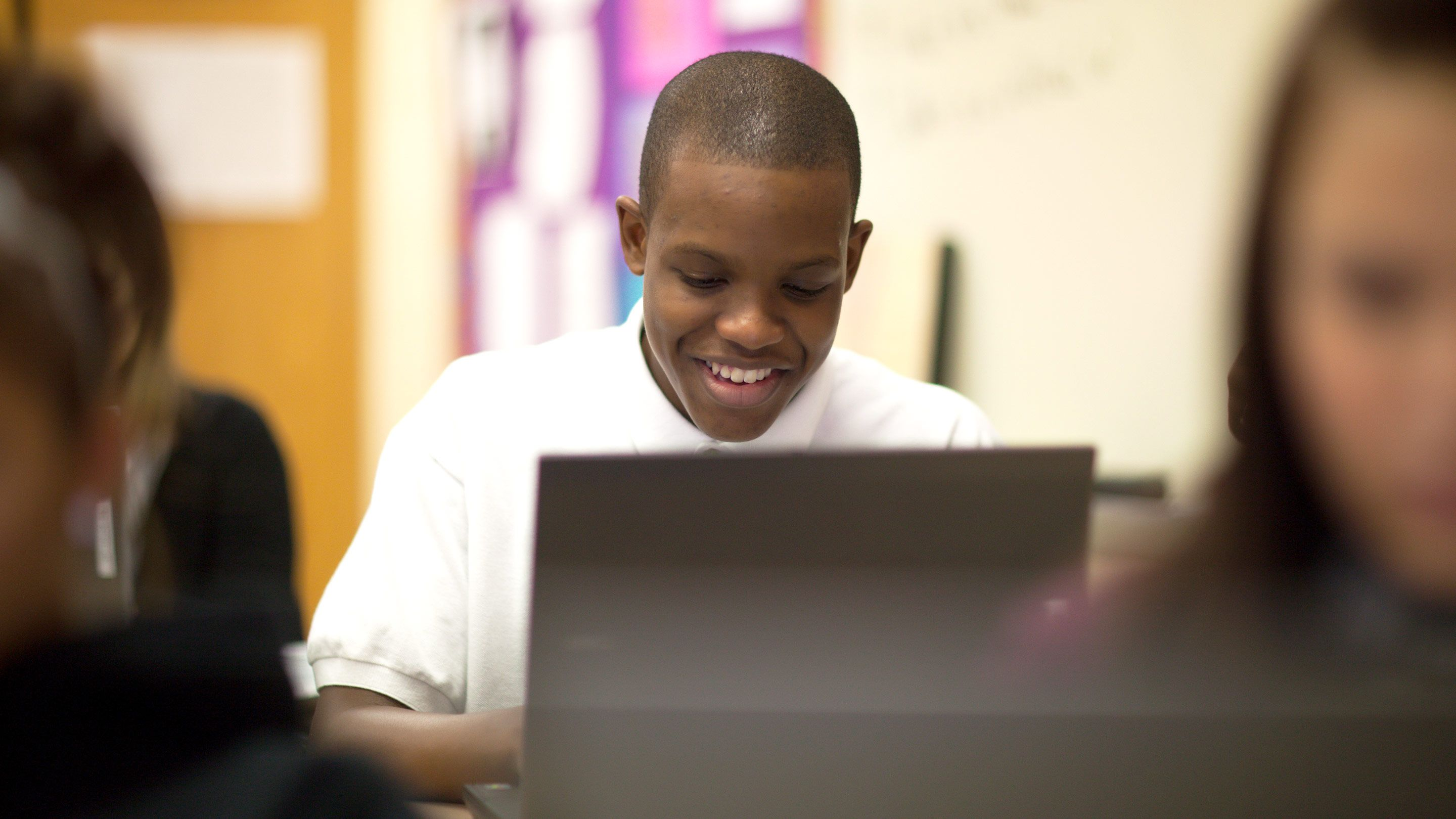 A high school student smiles confidently as he uses his computer.