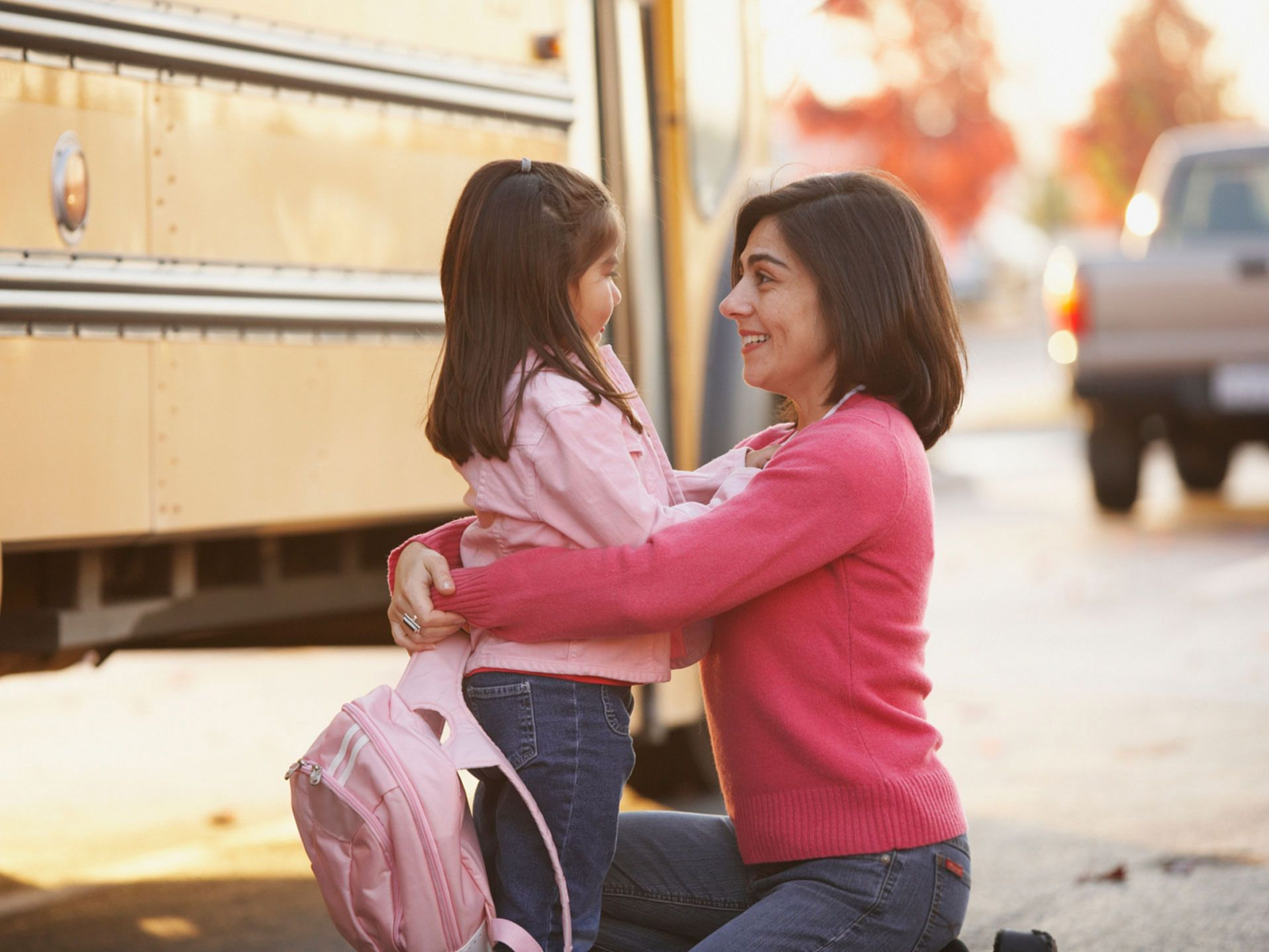 A photo of a parent and child in front of a school bus.
