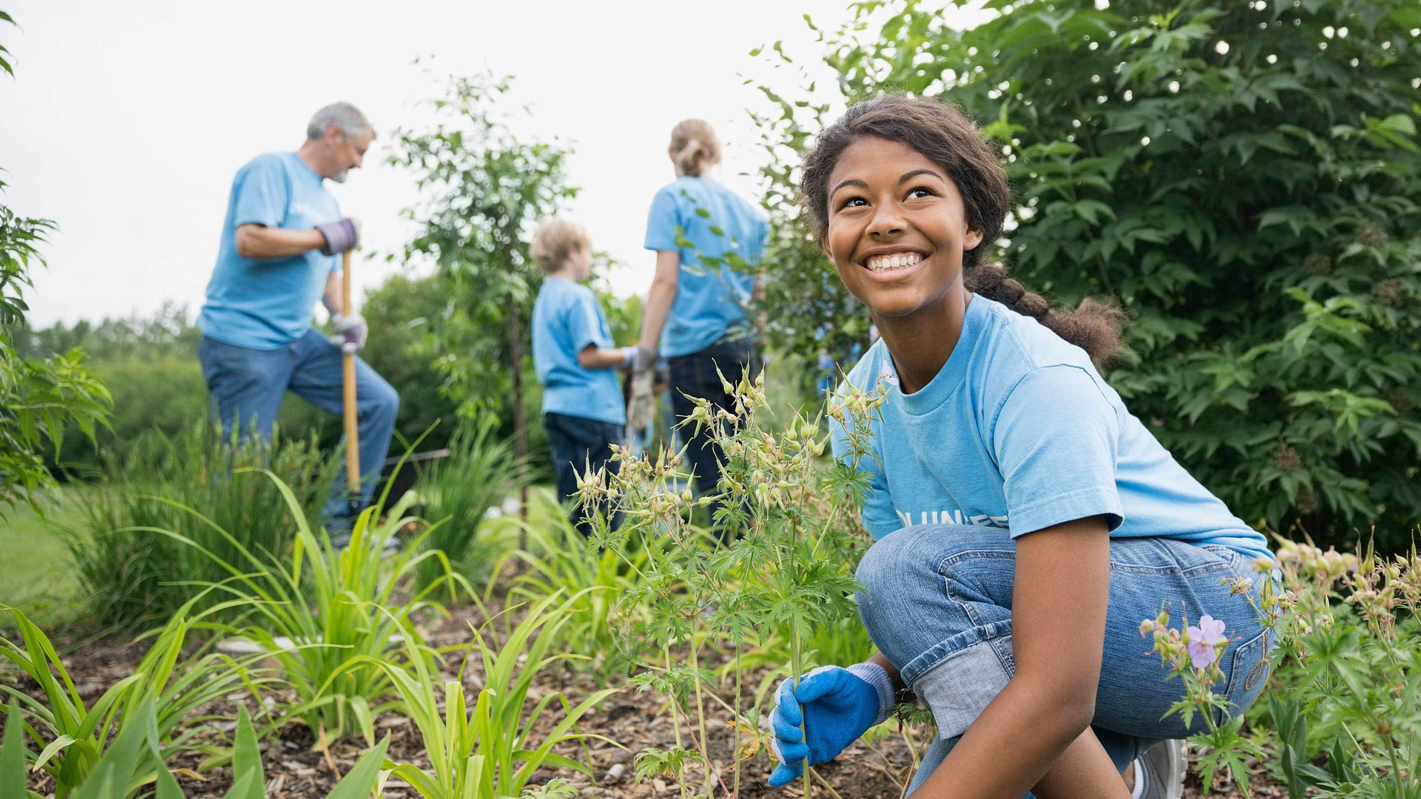 A girl in a blue shirt works in the garden