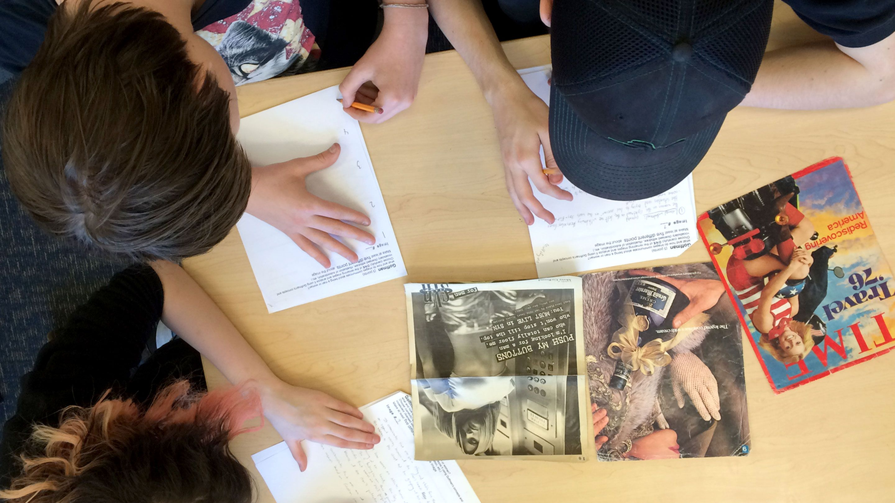 A few teenage students look at various ads and write responses on a handout.