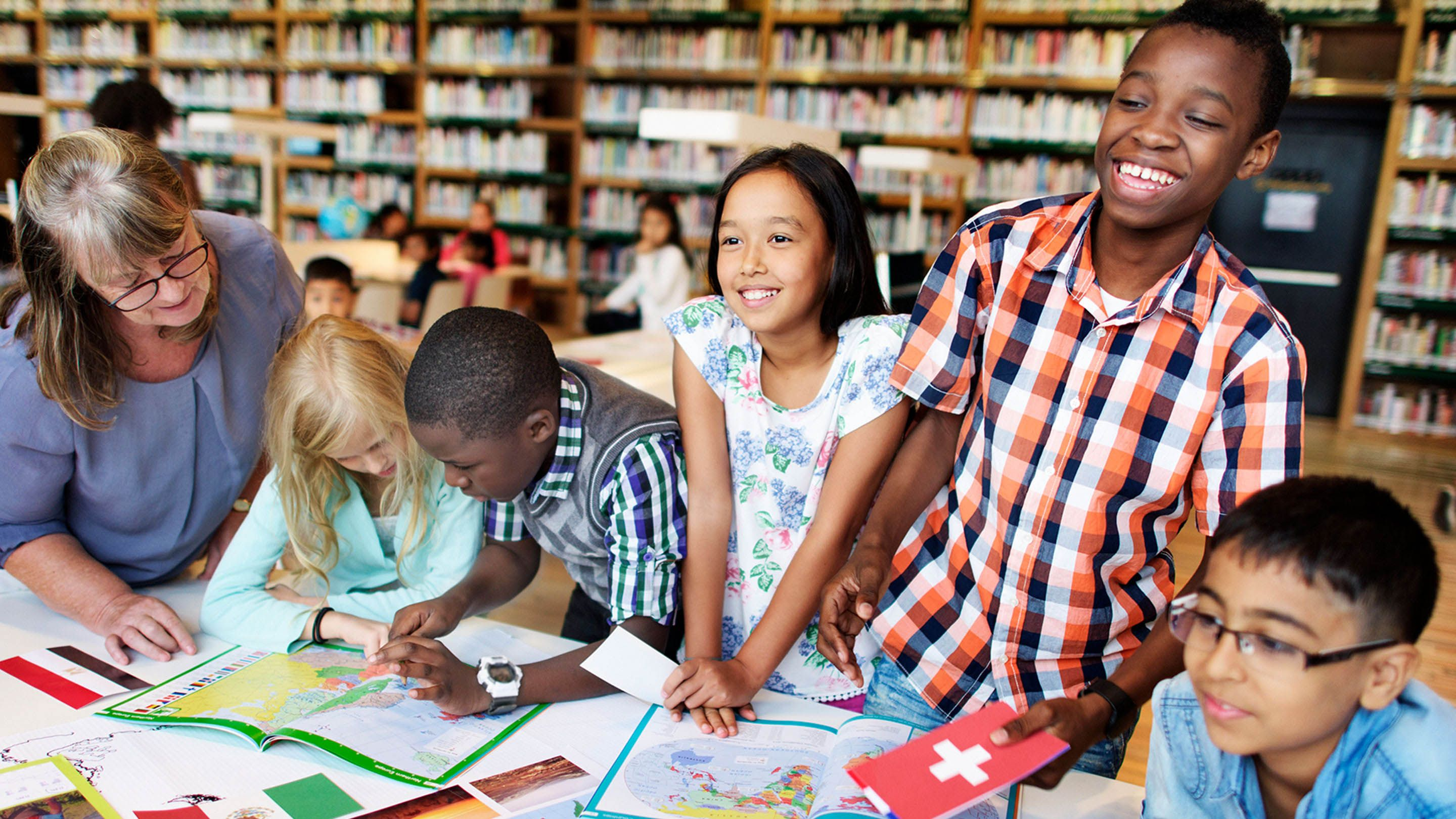 Five diverse, young students and a female librarian are standing by a table with atlases spread open in a library.