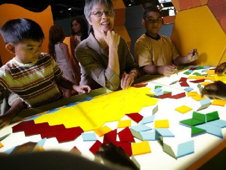 Kids and adult sitting around a table with geometric puzzle pieces