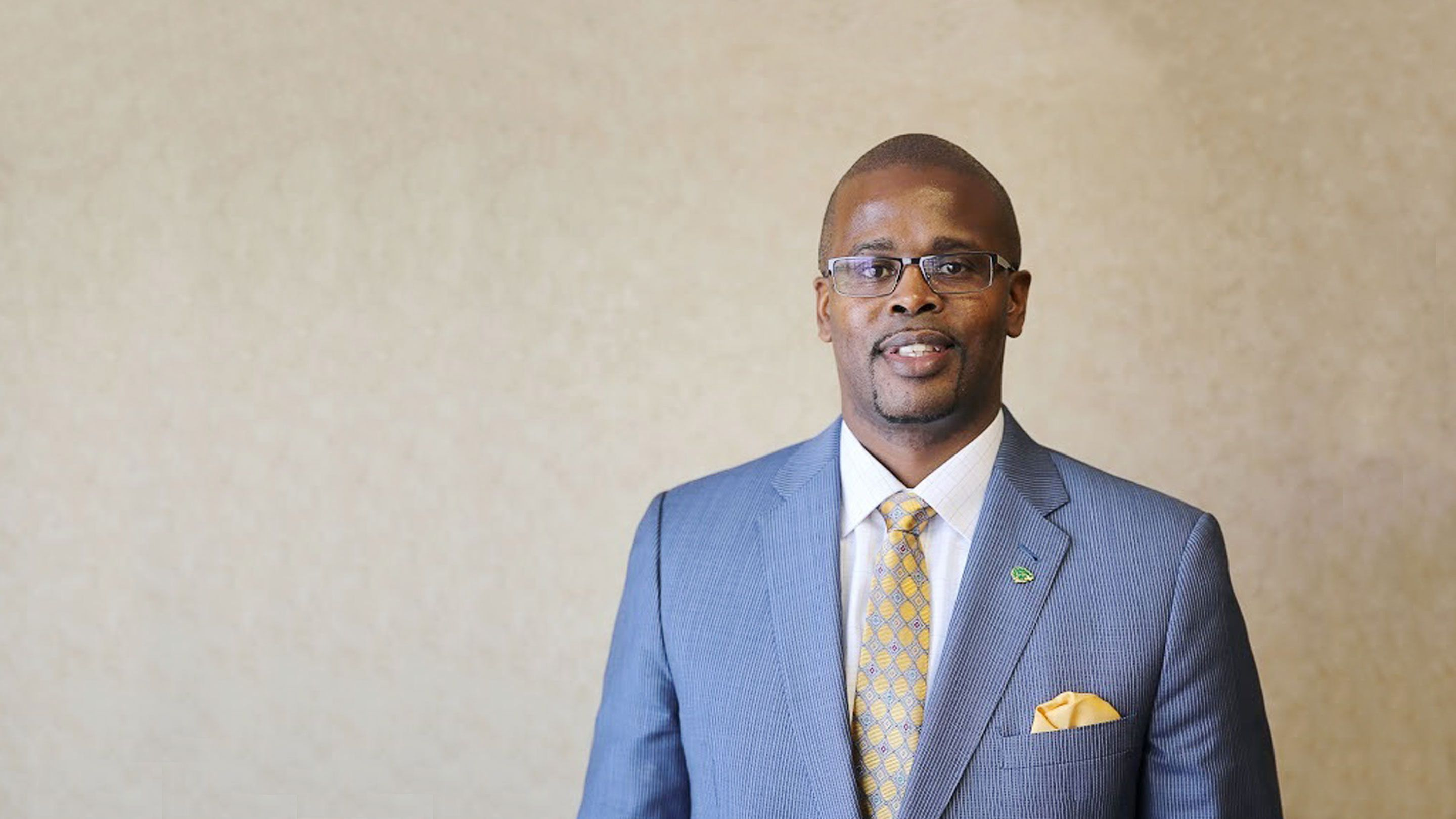 Photo of Antwan Wilson, a black male educator smiling in a suit.