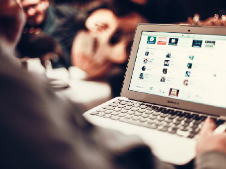 A photo of an adult on a laptop, with icons to various apps on the screen.