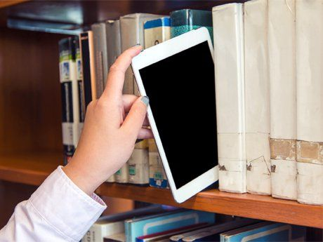 Hand pulling an iPad off the library shelf like a book